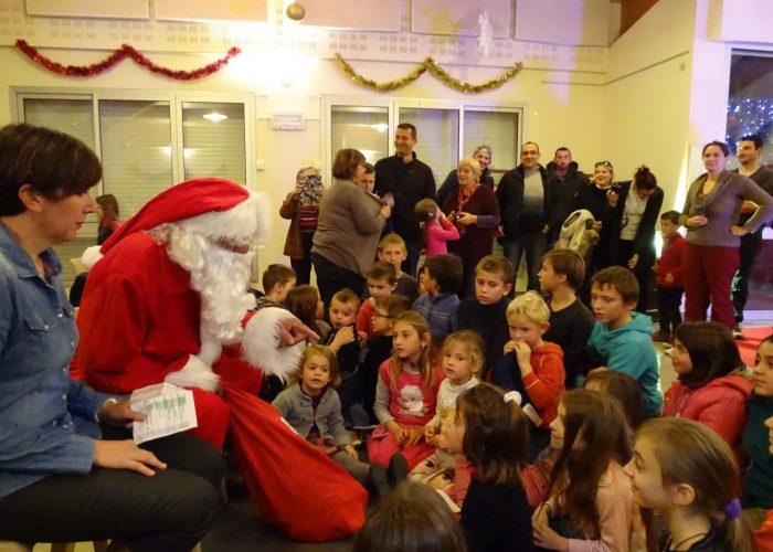 Le Père Noël apporte un cadeau à chacun des enfants invités par la municipalité